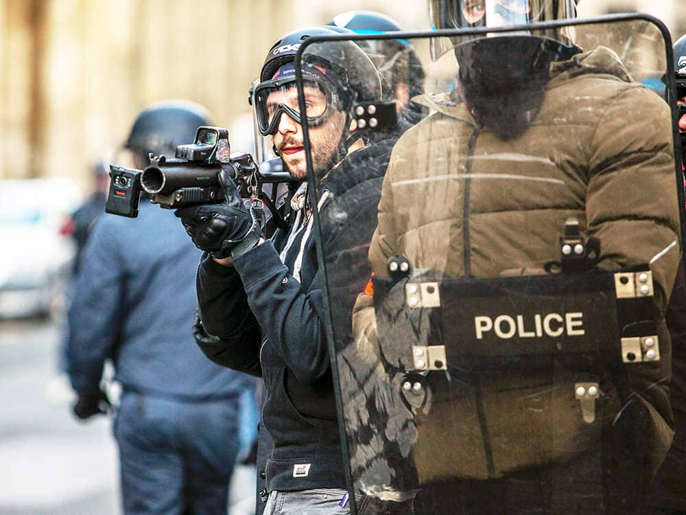 Two police officers use shield during riot control